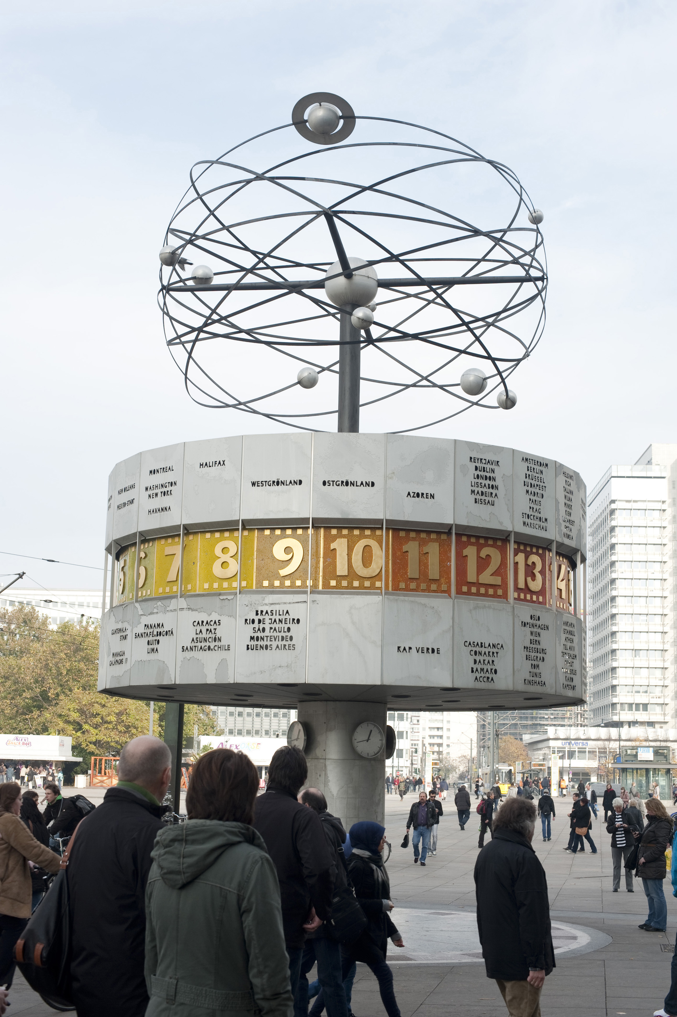 People viewing the World Time Clock, or Weltzeituhr, in Alexanderplatz, Berlin with the revolving planets above and the cylinder bearing 24 international time zones and names of major cities below