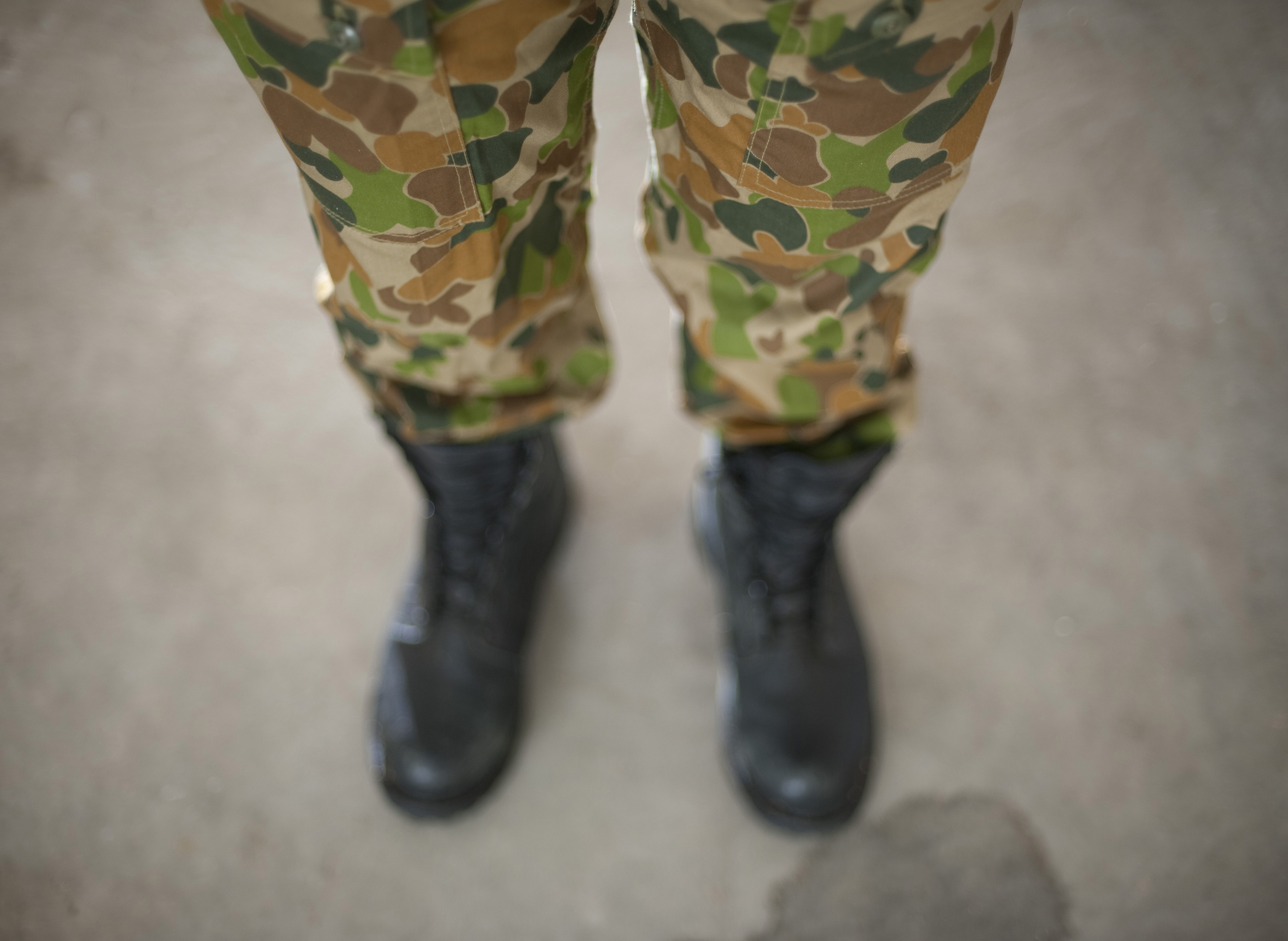 looking down at a soldier wearing army green camoflage pants, the disruptive pattern material is special designed to blend in with a range of background terrains and prevent the solder from being detected