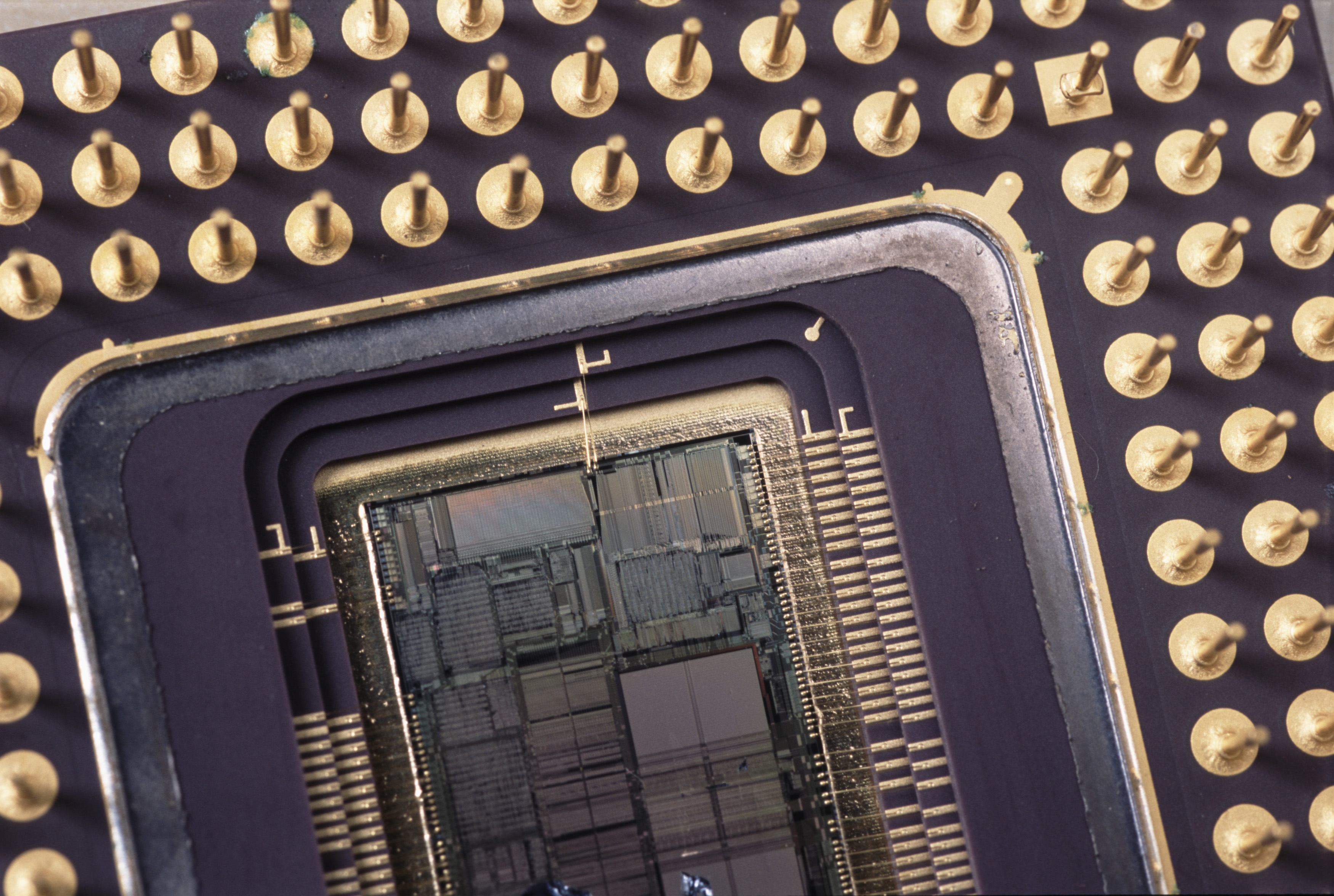 cutaway section showing the inside of a microprocessor chip. the silicone wafer of the chip show visible patterns outlining tarious arrays of memory, registers and other circuits used in the CPU