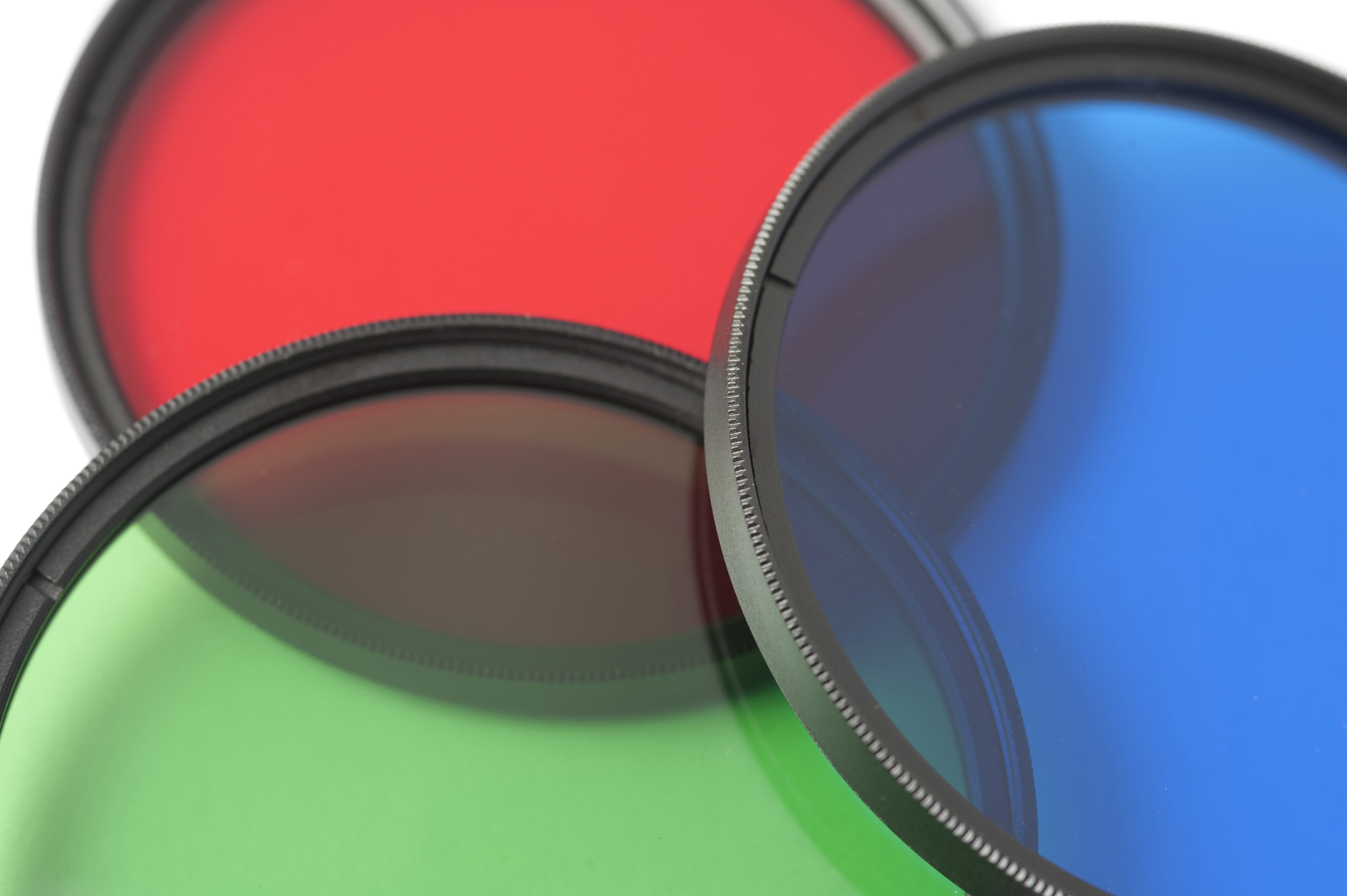 Set of three circular red, green and blue primary glass filters arranged to overlap, closeup detail